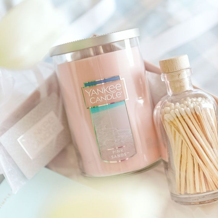 pink sands signature large tumbler candle next to glass bottle holding unlit matches