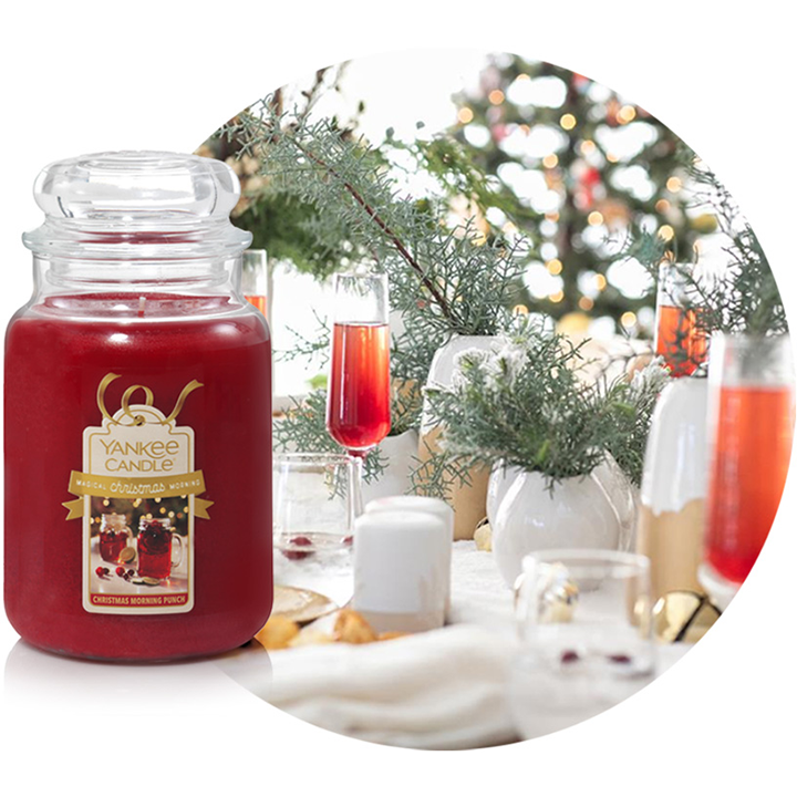 christmas morning punch scented candle next to holiday themed drinks