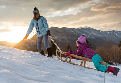 Woman pulling child up a hill on a sled